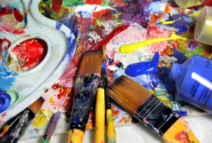 Art palette with a lot of paints and paintbrushes