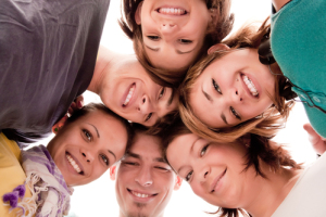 group of happy teenagers in circle – view from below