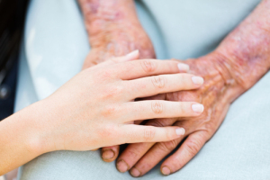 Caring woman hands over elderly hands being concept of trust and reliability.